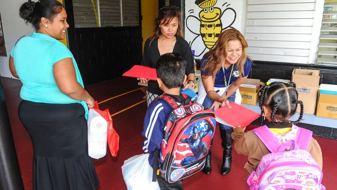Principal Darlene Castro, facing right, greets student with free school supplies before their the start of the first day of classes at Chief Brodie Memorial School in Tamuning on Thursday, Aug. 18.