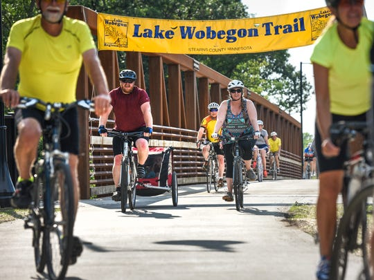 Bike riders cross the new bridge into Waite Park on the Lake Wobegon Trail extension Thursday, July 12, on a ride from the St. Joseph Trailhead.