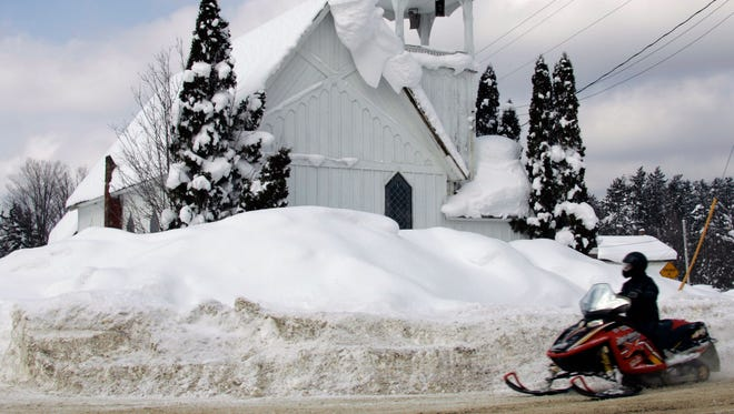 A person riding a snowmobile passes the Wesleyan Church in this 2007 photo taken in Redfield, N.Y.