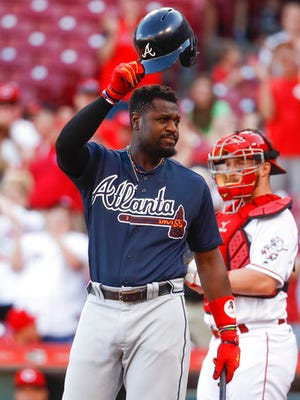 Atlanta Braves' Brandon Phillips, a former Cincinnati Reds second baseman, acknowledges the crowd cheering for him in the first inning of the team's baseball game against the Reds, Friday, June 2, 2017, in Cincinnati. (AP Photo/John Minchillo)