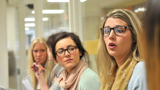 Callie Schroeder discusses a conflict mediation session March 23 before students arrive in the South Junior High School office. Schroeder, right, and fellow St. Cloud State University volunteers from the Conflict Resolution Center, Marissa Martin, center, and Britta Brolin, back, are all seniors studying relational communication studies.