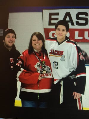 Logan Brummond poses with with parents Brian and Nicole in 2012 in this image of a post on the Friends of Wausau East Hockey Facebook page.