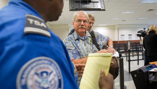 Passenger Don Heim, right, of Alpharetta, Ga., is briefed by Transportation Security Administration trainer Byron Gibson before going through a new expedited security line at Hartsfield-Jackson International Airport in Atlanta on Oct. 4, 2011.  The news that a man flew from Liberia to the U.S. after exposure to Ebola, and wound up in a hospital isolation ward, has led to calls for tougher measures to protect Americans, such as a ban on flights from countries hit by the epidemic.