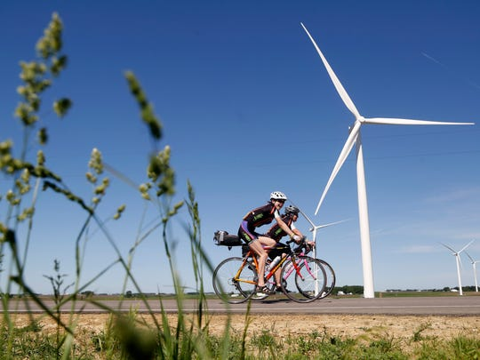 Riders make their way past windmills Sunday, June 4, 2017, during the first day of the RAGBRAI pre-ride route inspection in northeastern Iowa.