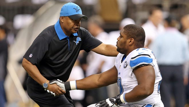 Detroit Lions coach Jim Caldwell, left, greets guard Laken Tomlinson before their game against the New Orleans Saints.
