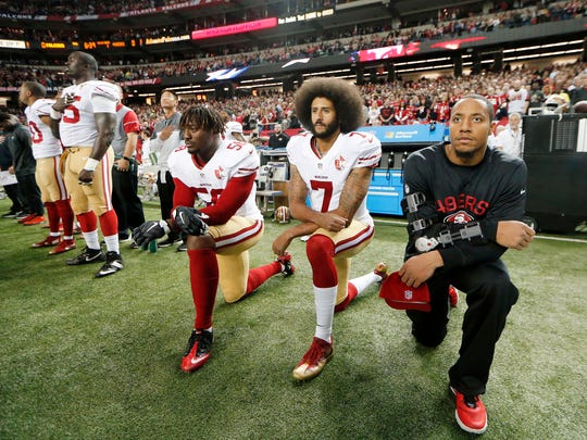 In this Dec. 18, 2016, file photo, San Francisco 49ers quarterback Colin Kaepernick (7) and outside linebacker Eli Harold (58) kneel during the playing of the national anthem before an NFL football game against the Atlanta Falcons in Atlanta. The blackballed quarterback was honored as Week 1 Community MVP by the players' union for his latest $100,000 donation and a back-to-school giveaway in New York City.
