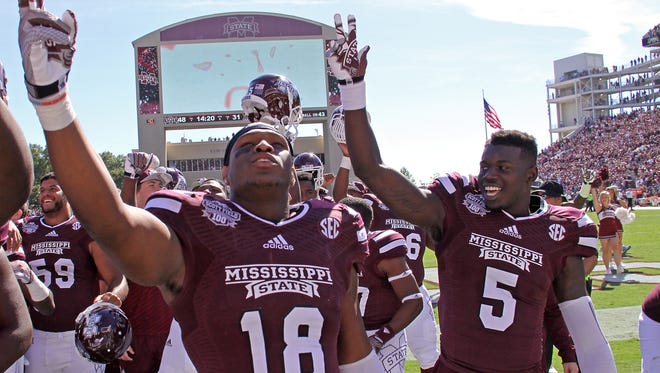 Mississippi State tight end Brandon Hill (18) and wide receiver Fred Brown (5) celebrate their 48-31 win over Texas A&M by singing the MSU Alma Mater at Davis Wade Stadium.
