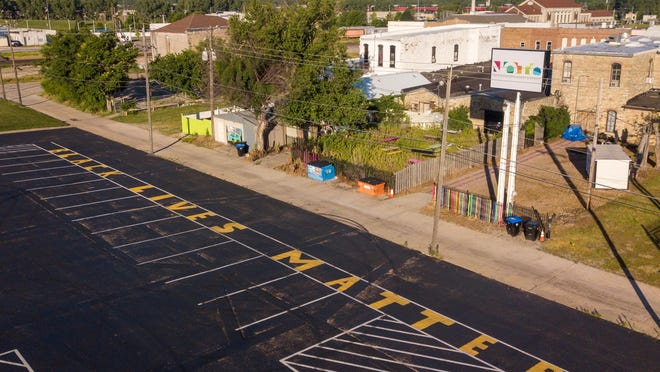 "The phrase ""Black Lives Matter"" is written in yellow paint on a parking lot East of NOTO Arts and Entertainment district in support of the national movement. The mural is set to be taken down ""within the week"" as some consider the painting ""vandalism,"" while others are frustrated and upset about the decision to wash it away. [June 2020 File Photo/The Capital-Journal"