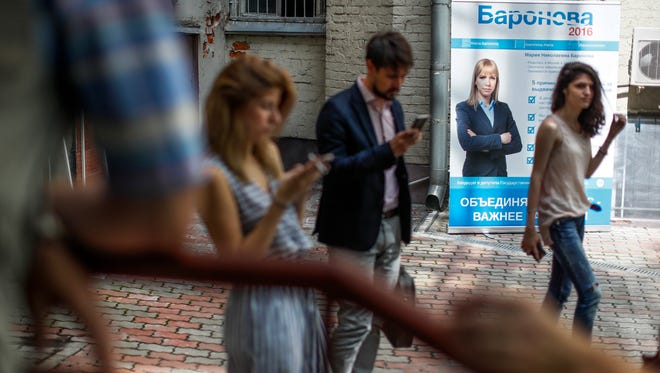 People stand by an election poster of opposition activist Maria Baronova on July 29, 2016. She is running in parliamentary elections in Moscow on Sept. 18, 2016.