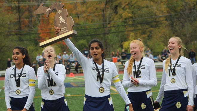 Detroit Country Day field hockey team members (from left) Anya Nayak, Olivia Bossardet, Anagha Nayak, Lauren Boos and Abbie Ashcraft celebrate with the Division 2 state championship trophy.