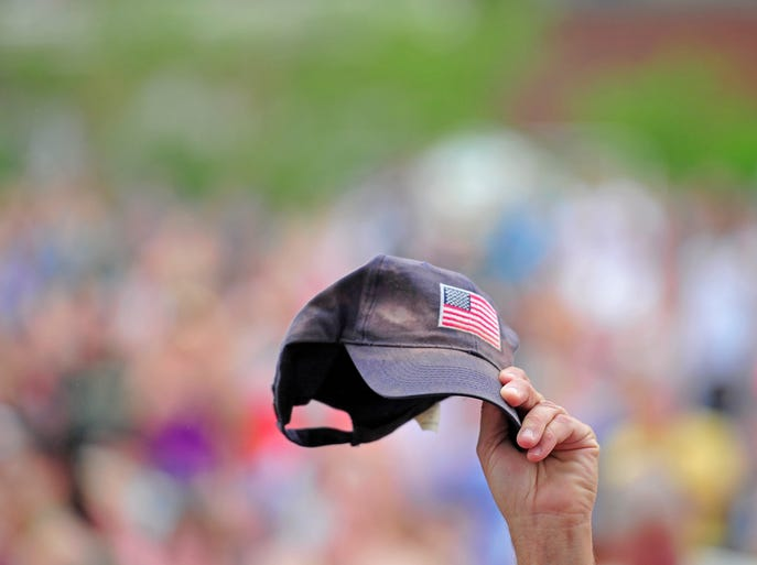 A fan holds up a hat with an American flag during the national anthem at the CMA Music Festival on Thursday, June 5, 2014, in Nashville.