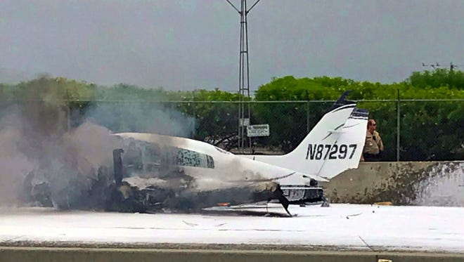 Flame and smoke erupt from a twin-engine prop jet after it crashed on Interstate 405, just short of the runway at John Wayne Orange County Airport, rear, in Costa Mesa on Friday.