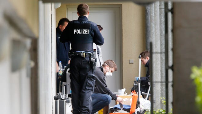 German police officers secure evidence in front of an apartment in Oberursel, Germany, Thursday, April 30, 2015. Chief of police for western Hesse state Stefan Mueller said authorities found a pipe bomb, 100 rounds of ammunition, parts of an assault rifle and a chemical that can be used to build a bomb during a raid overnight in the town of Oberursel. (AP Photo/Michael Probst)