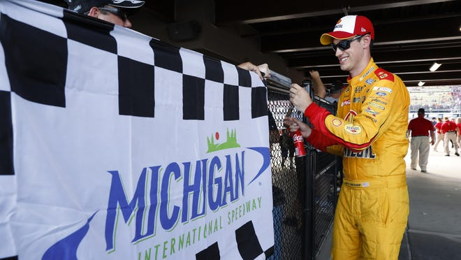 Joey Logano signs autographs for fans after winning the pole for Sunday's Pure Michigan 400 in the Irish Hills.
