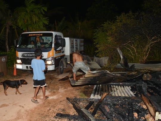 Mangilao resident John Edward Borja clears debris after a structure fire in Mangilao on April 24.