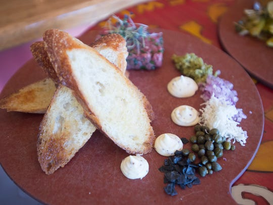 A plate of beef tartar is served with bread and sauce