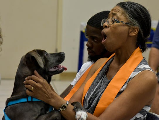 A church member calms her dog during a pet blessing