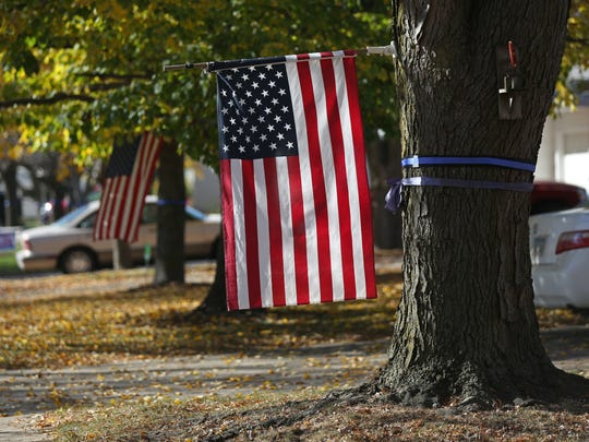 Blue ribbon wrapped trees line the neighborhood of