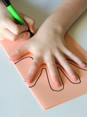 Trace your hand to make a handprint card that opens with a heart shape.