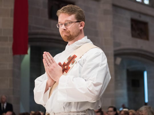 David Tomaszycki prays during the ordination Mass at the Cathedral of the Most Blessed Sacrament in Detroit.