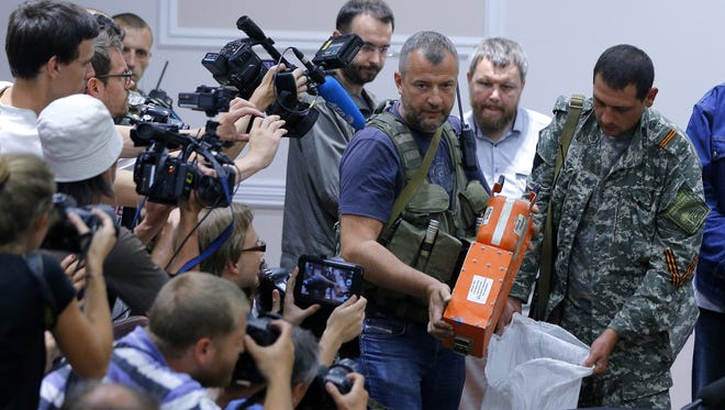 Separatist soldiers unveil the black boxes of the crashed Malaysian Air airliner MH17 to Malaysian officials during a press conference  in Donestk, Ukraine, on Monday.