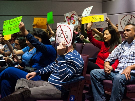 Protesters hold signs, expressing condemnation of ICE, during a sheriff candidate debate in Henderson County.
