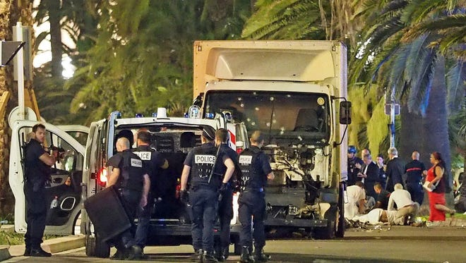 Police stand by as medical personnel attend a person on the ground, right, in the early hours of July 14, 2016, on the Promenade des Anglais in Nice, southern France, next to the lorry that had been driven into crowds of revelers.