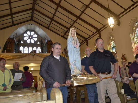 A statue of Mary is carried to the altar at the start