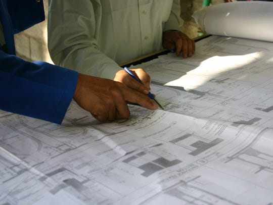 Architects on site with plan.