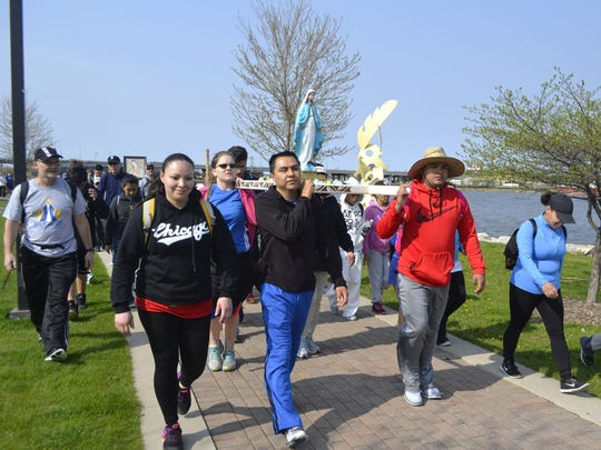 Pilgrims carry a statue of Mary while walking along the Fox River in downtown Green Bay during the fourth annual Walk to Mary on Saturday morning, May 7, 2016. The 21-mile walk from De Pere to The Shrine of Our Lady of Good Help in Champion included 1,050 people from 15 states.