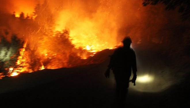 This photo obtained courtesy of the US Forest Service, shows a Hotshot walking the fire line on Thursday.