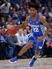 UK's Shai Gilgeous-Alexander drives to the basket against  Devonte' Graham of Kansas during the 2017 Champions Classic at the United Center in Chicago, IL on Tuesday, November 14, 2017.