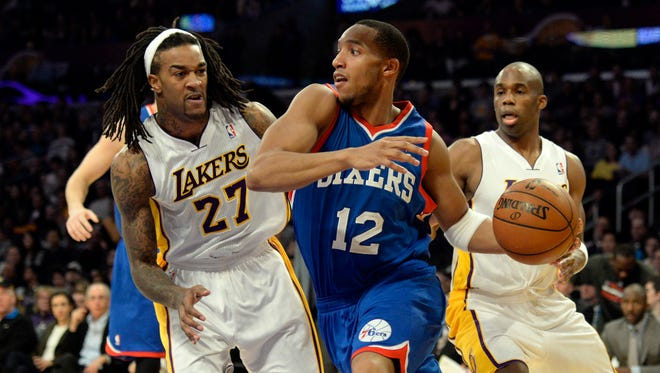 Philadelphia 76ers small forward Evan Turner (12) looks to pass under pressure from Los Angeles Lakers center Jordan Hill (27) during the first quarter at Staples Center.