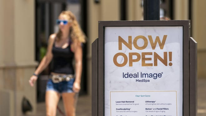 A shopper walks past a Now Open sign Monday at the newly reopened Palm Beach Outlets in West Palm Beach.