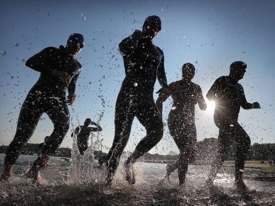 Athletes kick up a spray as they finish the swimming