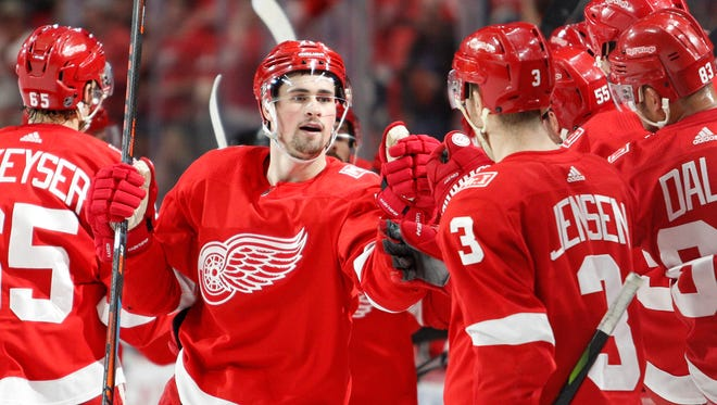 Detroit Red Wings center Dylan Larkin (71) celebrates with teammates after scoring a goal during the first period against the Montreal Canadiens at Little Caesars Arena on April 5, 2018.