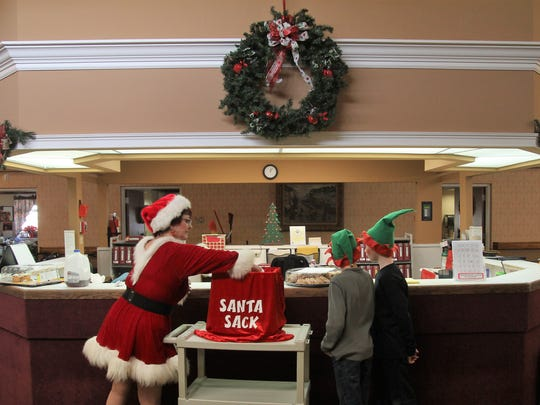 Sandy Hill, who portrays Sandy Claus, hands out candy at HRC Healthcare in Anderson.