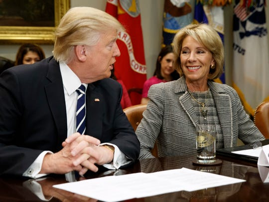 In this Feb. 14 file photo, President Donald Trump looks at Education Secretary Betsy DeVos as he speaks during a meeting with parents and teachers in the Roosevelt Room of the White House in Washington.