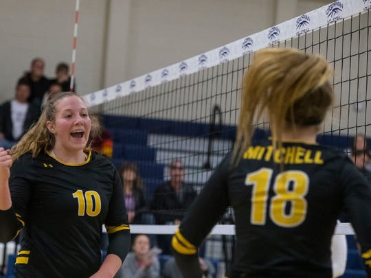 Mitchell's Mackenzie Miller (10) and Payton Morgan (18)  celebrate a point during a match against O'Gorman on Oct. 4, 2018.