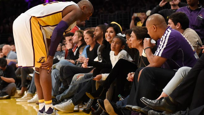 Los Angeles Lakers forward Kobe Bryant (left) talks to his family in the stands including wife Vanessa Bryant in the second half of a basketball game against the Indiana Pacers at Staples Center.