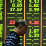 An investor walks past a screen that shows share prices in a security firm in Hangzhou, east China's Zhejiang province on July 27, 2015. China's benchmark Shanghai stock index slumped 5.22 percent in afternoon trade on July 27, dragged lower by worries over the economy. AFP PHOTO CHINA OUTSTR/AFP/Getty Images ORIG FILE ID: 542916965