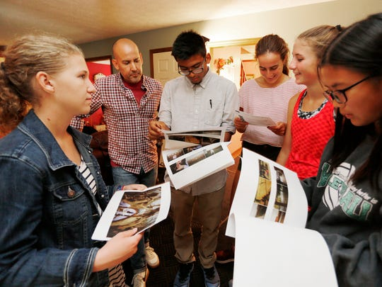 Robert Morales, second from left, shows West Lafayette students Abby Rhodes, from left, Anthony Aguilera, Titas Peraita, Ellie Tate and Aillen Huang agency story boards and director shooting boards during a break in shooting of a commercial for Orville Redenbacher popcorn Friday, October 7, 2016, in the University Farms subdivision in West Lafayette. The home selected for the shoot belongs to West Lafayette Community School Corp. Superintendent Rocky Killion. Killion said a location scout knocked on his door wanting to know if the production company could shoot the commercial there. Morales, with Society Films, is the producer on the job.