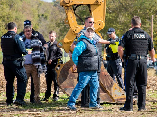 A police officer escorts one of about two dozen protesters that were arrested at a construction site for the Atlantic Sunrise natural gas pipeline on Monday. About 70 people turned out to show their dissent to the project, which is bringing the pipeline across property owned by the Adorers of the Blood of Christ. The Catholic order of nuns in western Lancaster County has been fighting the pipeline.