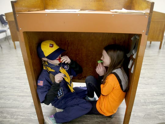 Brianna Richie, 8, and Annabeth Taylor, 7, hide under a podium and blow whistles during a lost hiker drill.