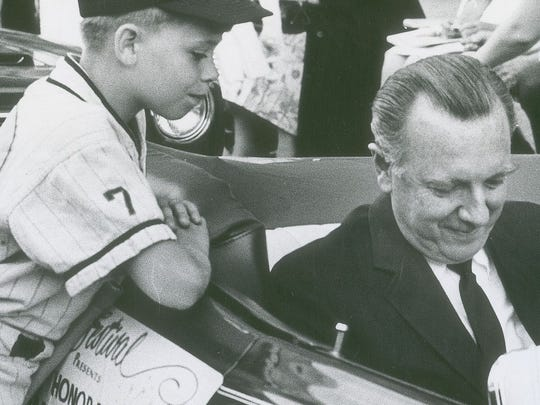 Veteran newsman Walter Cronkite signs an autograph for a Little League baseball player during the 1966 Indianapolis 500 Festival parade.
