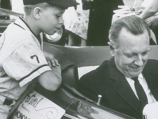 Veteran newsman Walter Cronkite signs an autograph