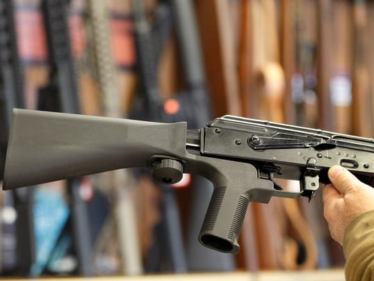 A bump stock device, (left) that fits on a semi-automatic