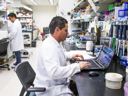 Post doctoral researcher Ming Yang, Ph.D., left, and graduate student Adrian Esqueda work in a lab at the BioDesign Institute at Arizona State University.