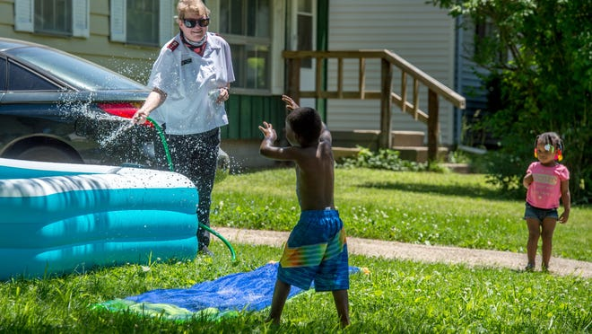 Capt. Lisa Thorson of the Salvation Army of Peoria teases a pair of kids with some cold water on a hot day as she and about 40 others walked the neighborhood around the Peoria Citadel during a community prayer walk Tuesday, June 2, 2020 in Peoria.