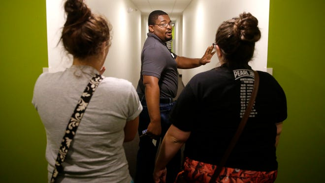 Brice Taoko, a resident assistant at Tech Village, answers questions from Karly Adamson and Morgan Klumpyan, who will be roommates for the upcoming school year. They were on a tour Monday of the new building Monday that's near Fox Valley Technical College.